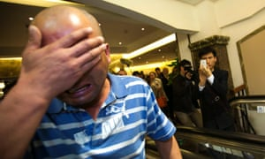 A relative of a Chinese passenger aboard the Malaysia Airlines MH370, covers his face after being told that the plane plunged into the Indian Ocean.