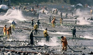 Workers in protective suits use pressure washers to clean oil from a beach after the 1989 spill