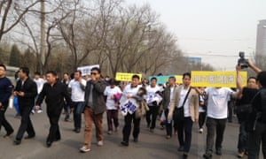 Families of the missing MH370 passengers march in protest through the streets of Beijing to the Malaysian embassy.
