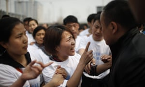 A relative of a passenger on missing Malaysia Airlines flight MH370 yells at a security personnel  while she attends a protest outside the Malaysian embassy in Beijing.