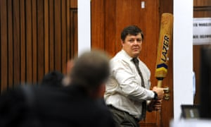 Forensic investigator Gerhard Vermeulen, with a cricket bat in hand, demonstrates on a mock-up toilet cubicle how the door could have been broken down, during the trial of Oscar Pistorius on March 12, 2014.