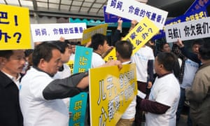Relatives of Chinese passengers of missing Malaysia Airlines flight MH370 distribute placards as they head to demonstrate at the Malaysian Embassy in Beijing.