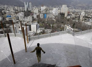 An Iranian worker goes down steps on the rooftop of a multi-storey building in Tehran's wealthy northern neighbourhood
