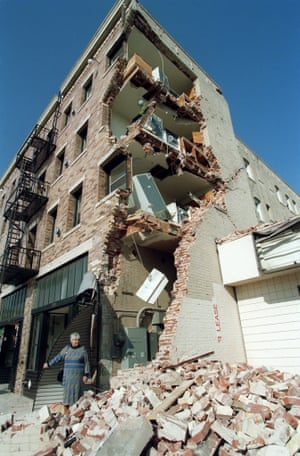 A woman walks over rubble after the Northridge earthquake, January 1994