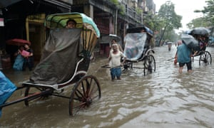 Rickshaw pullers carry passengers through water-logged streets in Kolkata