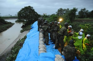 Japan Ground Self-Defence Force soldiers place sandbags to reinforce embankments on Shonai river