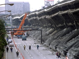 A giant crane pulls crushed cars out of the debris January 18 after the Hanshin Expressway was devastated during the worst earthquake in Japan