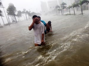 Filipinos wade through floodwaters along Roxas boulevard during Typhoon Nesat in Manila