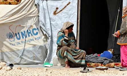 A Syrian refugee sits in front of her tent