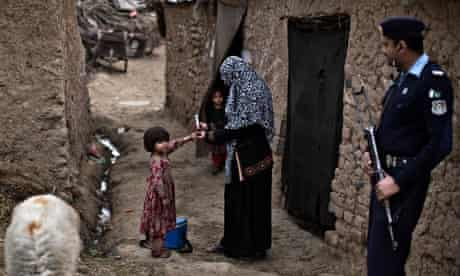 A Pakistani health worker marks the finger of a child after giving her a polio vaccine