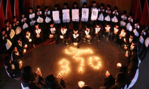 High school students hold candles during a vigil for passengers of the missing Malaysia Airline flight MH370 in Lianyungang, east China's Jiangsu province on March 25, 2014.