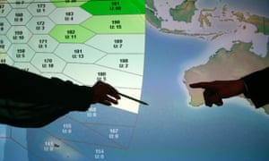 Member of staff at satellite communications company Inmarsat point to a section of the screen showing the southern Indian Ocean to the west of Australia, at their headquarters in London March 25, 2014.