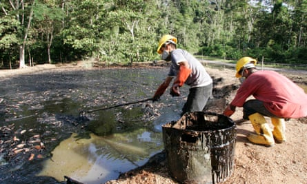 Oil workers clean up a contaminated pool in Taracoa, a section of the Amazon contaminated by oil pollution.