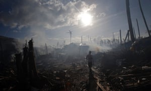 A man walking through smoke from fires in a part of Tolosa devastated by Typhoon Haiyan
