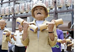 Elderly people work out with wooden dumb