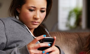 Teenage girl looking at cellphone cyber bullying