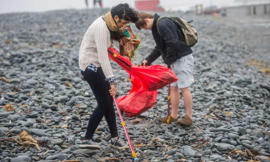 Rubbish on British beach : Young university students clean litter off the beach at Aberystwyth Wales