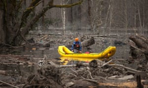 A man in a search and rescue boat floats through the debris after the mudslide near Oso, Washington.