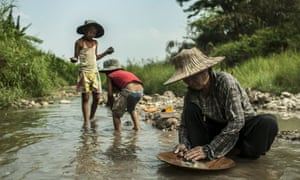 Petong pans for gold as her children play in the water.