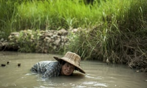 Petong shovels mud as she pans for gold.