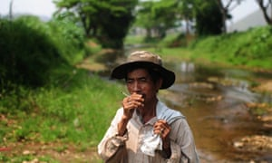 A worker smokes after he finishes his work in the river in Lampang.