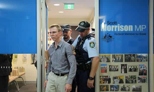 Justin Whelan is led by police from Scott Morrison's office