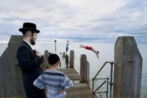 A Jewish man and his son watch a couple of young locals go for an afternoon swim. A Fine Beginning Wales photography collective