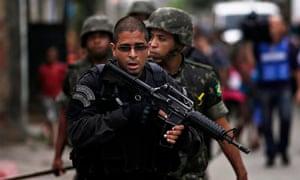 Policeman escorts Brazilian Army in Mare slums complex in Rio de Janeiro