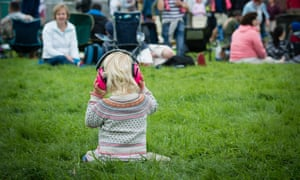 A child at a festival wearing headphones