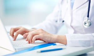 Close-up of a medical worker typing on laptop