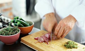 A man chopping onions and herbs