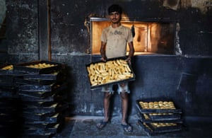 Sameer, a 20-year-old worker, poses inside a bakery at a slum in Mumbai. Sameer said that he wants the new government to reduce food prices.