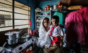 Nasreen Bano, a 22-year-old housewife, poses with her four-year-old son inside their one-room apartment in a residential building in Mumbai. Nasreen said that she wants the new government to control the rising prices of food commodities.