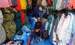 Mohammad Sabir, a 20-year-old salesman, poses inside his roadside shop at a market in Mumbai March 24, 2014. Sabir said that he wants less corruption from the new government after the elections.