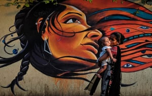 A mother kisses her child as she walks past graffiti in Mumbai.