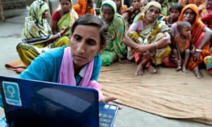 A Bangladeshi woman brings a laptop to a village to help people access the internet.