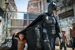 Children play around a man dressed as Batman at the Favela do Metro slum in Rio de Janeiro, Brazil.