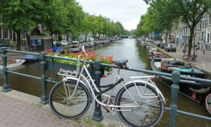 Bicycle parked up over a canal in Amsterdam.
