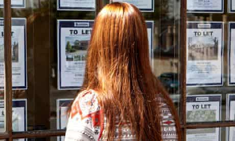 Woman looks into the window of an estate agent