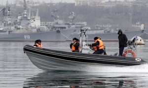 Russian navy crew members on a patrol boat guard the Russian military ships of the Black Sea Fleet with destroyers 'Smetlivyy' (back L) and 'Kerch' (back R) in the port of Sevastopol, Crimea, Ukraine, on 2 March 2014.