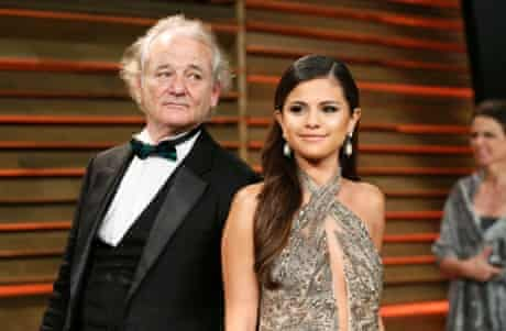 "Actor Bill Murray ""photobombs"" singer Selena Gomez as they arrive for the 2014 Vanity Fair Oscars Party"