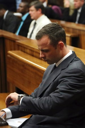 Oscar Pistorius looks at his watch as the start of his trial is delayed