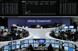 Traders are pictured at their desks in front of the DAX board at the Frankfurt stock exchange March 3, 2014.