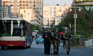 Armed policemen and paramilitary policemen patrol a street near Kunming railway station