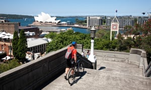 Cities: cyclist carries bike down the steps with the Sydney Opera House in the background