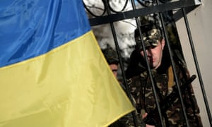 Ukrainian soldiers look out through a gate from behind a Ukrainian flag as they wait inside the Sevastopol tactical military brigade base near Belbek in Sevastopol on March 3, 2014. Russian forces have given Ukrainian soldiers an ultimatum to surrender their positions in Crimea or face an assault, a Ukrainian defence ministry spokesman said.