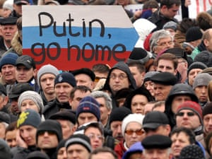 A man holds a sign against Putin as 30,000 people rally in the Independence Square