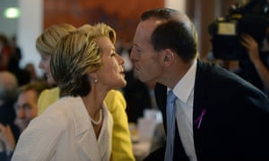 Tony Abbott greets Julie Bishop as they attend the International Women's Day Parliamentary Breakfast.