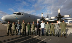 Australian Prime Minister Tony Abbott poses with leaders of international military operations currently based in Australia searching for the missing Malaysia Airlines Flight MH370 in front of a Royal Australian Air Force P-3C Orion search aircraft.