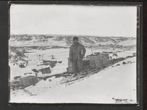 """Henry 'Birdie' Bowers, Cape Evans, October 1911  (""""Portrait of Bowers standing on snow beside a pile of boxes and a sledge loaded with boxes. Hills in background."""")."""